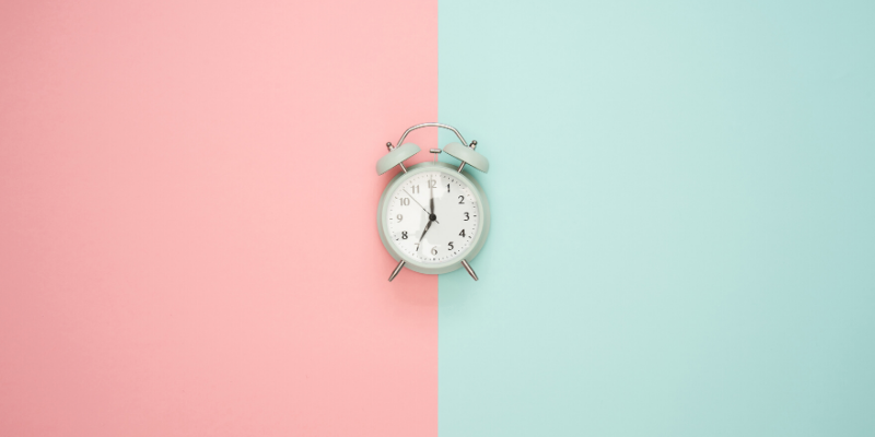 picture of clock against pink and green background. grow airbnb business for free